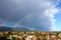 Double rainbow in the sky after rain. Hetauda, Nepal. Double rainbow in the cloudy sky after the strong rain above roofs of small nepali village royalty free stock image