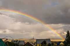 A double rainbow in the village. Above the houses Stock Images