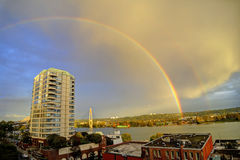 Double rainbows over city and across river at sunset Stock Photos
