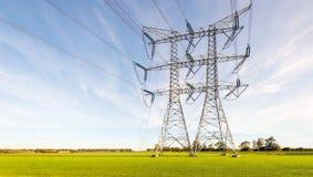 Double rangée des lignes électriques et des pylônes dans une terre rurale néerlandaise plate photos libres de droits