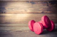 Double red dumbbells 1 kg on wood background. Royalty Free Stock Photography