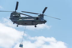 Double rotor, heavy airlift, military helicopter, in flight, carrying cargo. Royalty Free Stock Images