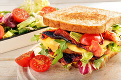 Double sandwich with bacon cheese and vegetables on wooden backg Stock Photography