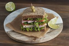 Double sandwich with ham, cheese, lettuce, tomato and green olives. Whole grain bread. Snack or take away food. Black background. Isolated stock image