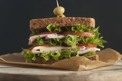 Double sandwich with ham, cheese, lettuce, tomato and green olives. Whole grain bread. Snack or take away food. Black background. Isolated royalty free stock images