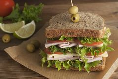 Double sandwich with ham, cheese, lettuce, tomato and green olives. Whole grain bread. Snack or take away food. Black background. Isolated royalty free stock photos