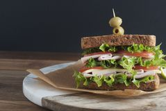 Double sandwich with ham, cheese, lettuce, tomato and green olives. Whole grain bread. Snack or take away food. Black background. Isolated stock photos