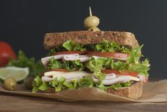 Double sandwich with ham, cheese, lettuce, tomato and green olives. Whole grain bread. Snack or take away food. Black background. Isolated stock images