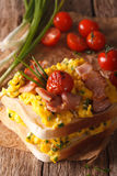 Double sandwich with scrambled eggs, bacon and tomatoes close-up Royalty Free Stock Image