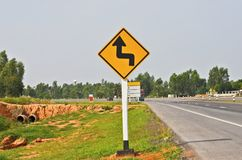 Double sharp curve warning street sign. Bee new asphalt road in the countrye royalty free stock image
