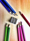 Double sharpner and pencils. Grouped colouring pencils and metallic sharpner Royalty Free Stock Image