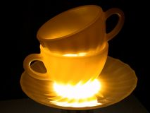 Double shine cup and plate. The ceramic cups and plate illuminated from below Royalty Free Stock Photo