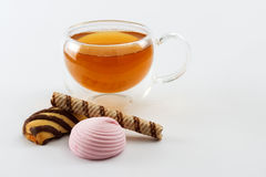 Double sided wall glass cup full of green tea with sweets and biscuits Stock Images