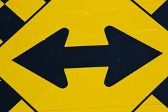 Double signe noir jaune de route de panneau routier de flèche Images stock