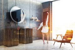 Double sink in concrete bathroom corner, woman. Woman in modern bathroom with concrete walls and floor and two wooden sinks with a round mirror hanging above stock images