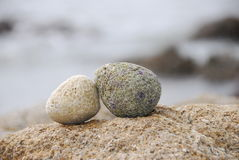 Double stone. Lying together on another big rock on the beach,the background is sea and rocks Royalty Free Stock Photo