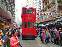 Double-storey-tram runs through a market in Hong Kong. Hong Kong, China - February 10, 2016: A red double-storey-tram runs through a market in Hong Kong, North Stock Photo