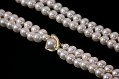 Double strand pearls. Double strand of pearls on black with gold and diamonds Stock Images
