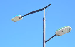 Double street lamp. A photo of a double street lamp on a blue sky background Royalty Free Stock Image