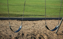 Double swings. Two swings with grass background stock image