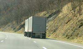 A Double Trailer Semi Truck Driving Through The Mountains Stock Photos