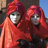 Double Trouble. Two women dressed for Carnivale,the Mardi Gras of Europe, in Saint Marks Square,Venice,Italy Royalty Free Stock Images