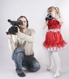 Double video shooting. Professional cameraman and little girl with home video camera shooting at studio Stock Photography