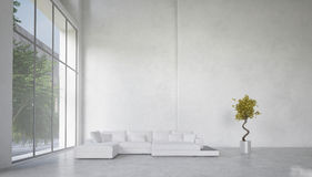 Double volume spacious living room interior. With huge panoramic windows overlooking a garden and a corner unit white lounge suite against a bare white wall Stock Images