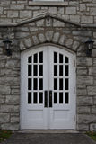 Double white doors framed with old stone work. Stock Photo