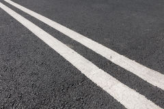 Double white line diagonally across the road Stock Images