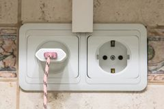 Double white outlet on the tile kitchen with a charge from the mobile phone.  Royalty Free Stock Photography
