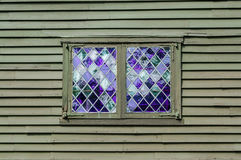 Double window with purple panes in a diamond pattern in the wall of a colonial building Stock Photography
