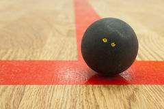 Double yellow dot squash ball on t-line. Double yellow dot official black squash ball on the red t-line in squash court stock images