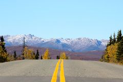 DOUBLE YELLOW HIGHWAY LINES IN MOUNTAIN SCENERY. Highway with double yellow lines leading to snow capped mountains and blue sky with fall forrest trees on Royalty Free Stock Photo