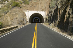 Double yellow-line leads to a tunnel through a mountain on highway 33 in Ojai, Ventura County California Stock Photo