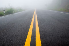 Double yellow lines. On the road with fog Stock Photography