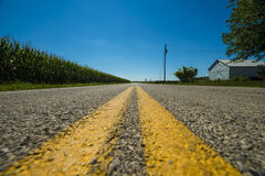Double yellow lines. Down a country road along corn field and barns with blue skies Royalty Free Stock Photography