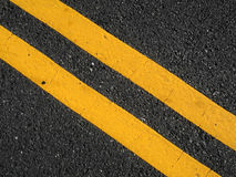 Double Yellow Lines. Freshly,painted diagonal double yellow traffic lines on road surface Stock Photos