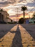 Double yellow lines on the street leading to a power line tower against sunset sky Stock Photos