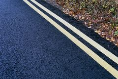 Double Yellow No Parking Lines Tarmac. Double yellow no parking road markings on tarmac from England UK Essex royalty free stock images