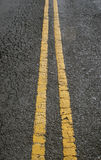 Double yellow parallel lines in concrete road. Perspective angle cracking pavement Stock Images