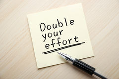 Double Your Effort. Text Double Your Effort is written on the sticky note with ball pen aside Royalty Free Stock Image