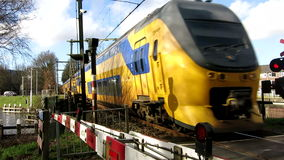 Doubledeck train passing by crossing. A Dutch Railways (NS) train passing by a railroad crossing guarded by barriers, warning lights and -bells stock video