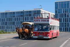 A doubledecker sightseeing bus and a horse carriage  doing a sigh. Berlin, Germany - may 27, 2017: A doubledecker sightseeing busand a horse carriage  doing a Royalty Free Stock Photo