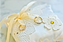 Doubles anneaux d'or sur l'oreiller blanc image stock