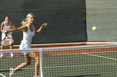 Doubles Player Hitting Tennis Ball With Backhand. View of female doubles tennis player hitting tennis ball with backhand on court Stock Images