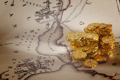 Doubloons and Treasure Map. Old map of Atlantis and a pile of gold doubloons Stock Photography