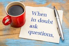 When in doubt ask questions. Handwriting on a napkin with a cup of coffee Royalty Free Stock Image
