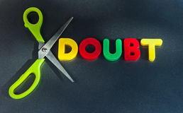 Doubt: cut it out. Text 'doubt' in colorful upper case letters with a pair of scissors showing concept cut out or remove doubt, dark background stock photos