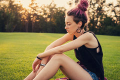 Doubt, dreams, failure, worry concept. Sad young woman with dreadlocks sitting on the ground. Doubt, dreams, failure, worry concept Stock Photography